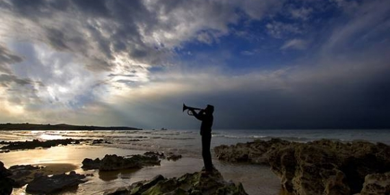 Trumpet player beside sea